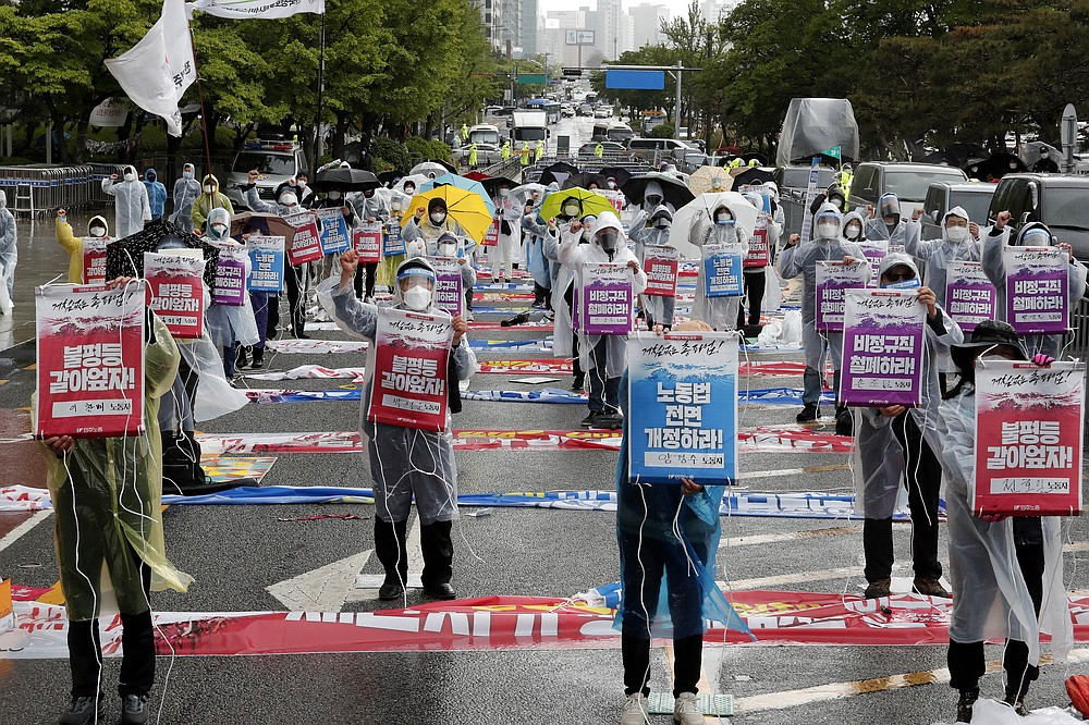 """Members of the Korean Confederation of Trade Unions stage a May Day rally demanding better working conditions and expanding labor rights in Seoul, South Korea, Saturday, May 1, 2021. The signs read: """"Let's solve inequality."""" (AP Photo/Ahn Young-joon)"""
