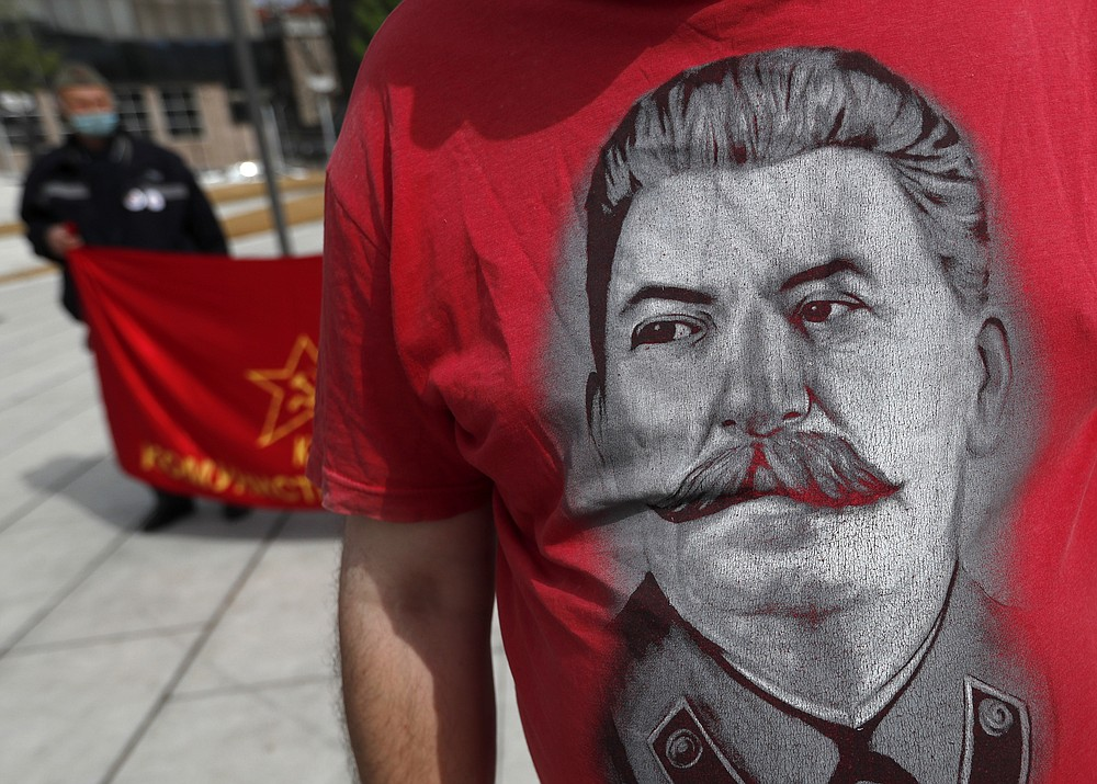 A man wearing a shirt with the image of former Soviet dictator Joseph Stalin attends a May Day rally on International Workers Day in Belgrade, Serbia, Saturday, May 1, 2021. Activists marked May Day with defiant rally. (AP Photo/Darko Vojinovic)