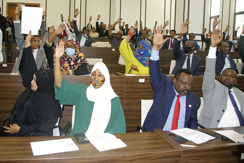 Somalia lawmakers raise their hands to endorse a direct election, during a parliamentary session, in Mogadishu, Somalia, Saturday, May 1, 2021. The controversial two-year term extension for Somalia's president has evaporated after intense public pressure as the lower house of parliament has approved his request to instead support efforts to organize the country's long-delayed national election.  (AP Photo/Farah Abdi Warsameh)
