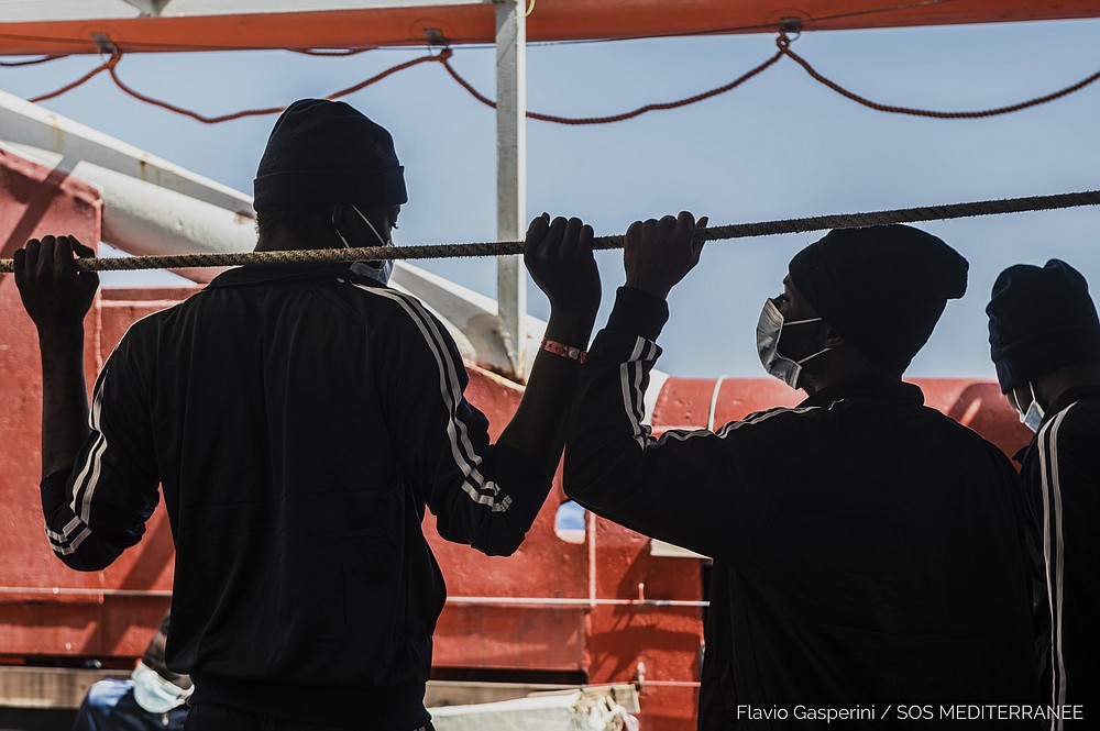 In this photo taken Thursday, April 29, 2021 migrants look at the sea from aboard the Ocean Viking during its navigation in the Mediterranean Sea.  SOS Mediterranee said Saturday May 1, 2021 the Ocean Viking was sailing toward a Sicilian port with 236 migrants who were rescued days earlier in the Mediterranean from human traffickers' boats, while separately, Italy's coast guard and border police vessels brought 532 migrants rescued during the night to a tiny Italian island.  (Flavio Gasperini/SOS Mediterranee via AP)