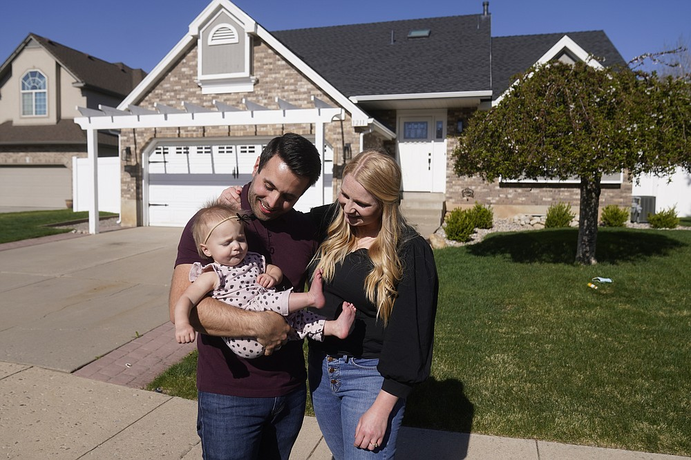 FILE - Matthew Clewett, 26, holds his daughter Nellie, while his wife Bethany looks on at their home Thursday, April 29, 2021, in Kaysville, Utah. Utah is one of two Western states known for rugged landscapes and wide-open spaces that are bucking the trend of sluggish U.S. population growth. The Clewett's want to have a large family like the ones they grew up in, but high housing costs could put a serious damper on that plan. The couple bid on at least 10 houses in northern Utah before they could close on a starter home for themselves and their infant daughter. (AP Photo/Rick Bowmer)