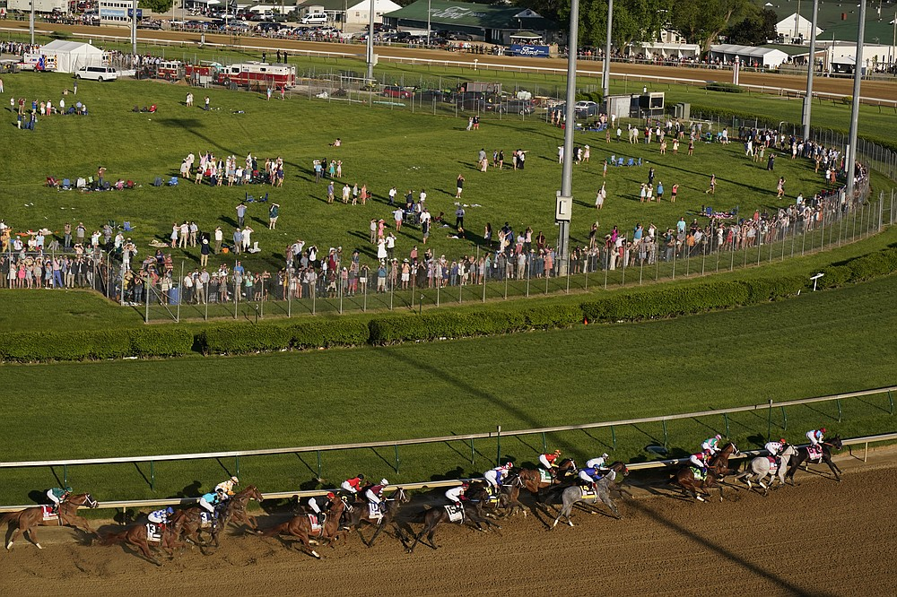 Medina Spirit, right, with John Velazquez aboard, leads the field around the first turn on the way to winning the 147th running of the Kentucky Derby at Churchill Downs, Saturday, May 1, 2021, in Louisville, Ky. (AP Photo/Charlie Riedel)