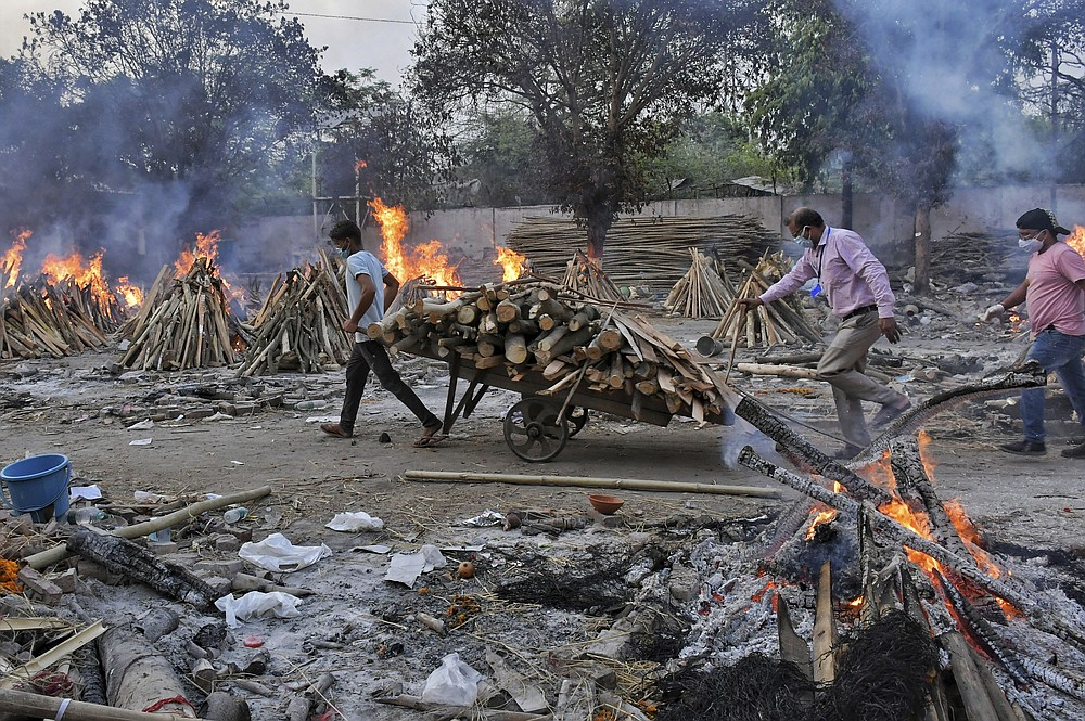 A worker carries wood on a hand cart as multiple funeral pyres of COVID-19 victims burn at a crematorium on the outskirts of New Delhi, India, Saturday, May 1, 2021. India on Saturday set yet another daily global record with 401,993 new cases, taking its tally to more than 19.1 million. Another 3,523 people died in the past 24 hours, raising the overall fatalities to 211,853, according to the Health Ministry. Experts believe both figures are an undercount. (AP Photo/Ishant Chauhan)