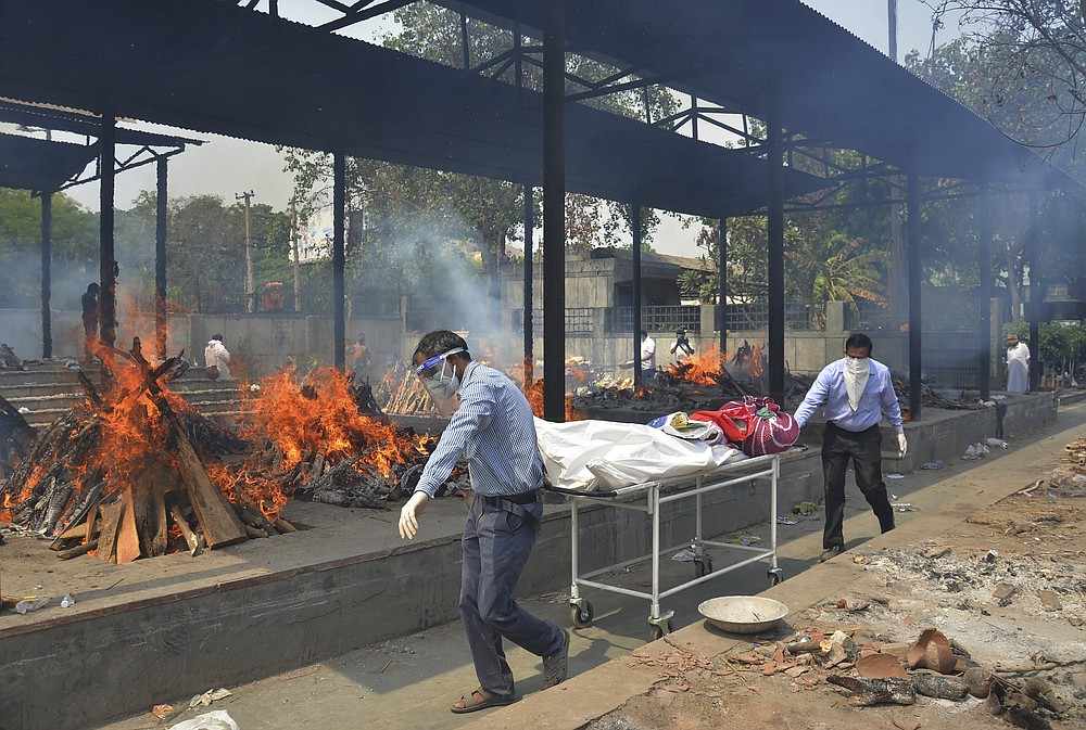 Relatives carry the body of a person who died of COVID-19 as multiple pyres of other COVID-19 victims burn at a crematorium in New Delhi, India, Saturday, May 1, 2021. India on Saturday set yet another daily global record with 401,993 new cases, taking its tally to more than 19.1 million. Another 3,523 people died in the past 24 hours, raising the overall fatalities to 211,853, according to the Health Ministry. Experts believe both figures are an undercount. (AP Photo/Amit Sharma)