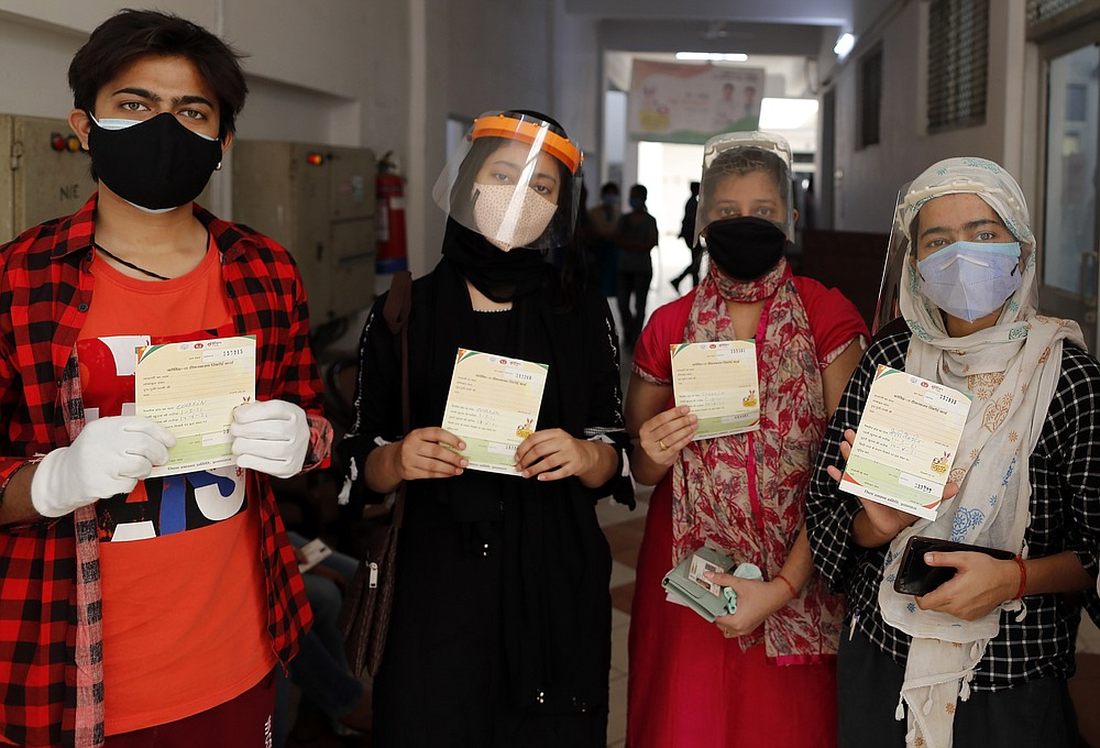 Shashank Shekhar, 18, left, stands with his sisters displaying their vaccination cards after receiving COVID-19 vaccine at a hospital in Prayagraj, India. Saturday, May 1, 2021. In hopes of taming a monstrous spike in COVID-19 infections, India opened vaccinations to all adults Saturday, launching a huge inoculation effort that was sure to tax the limits of the federal government, the country's vaccine factories and the patience of its 1.4 billion people. (AP Photo/Rajesh Kumar Singh)