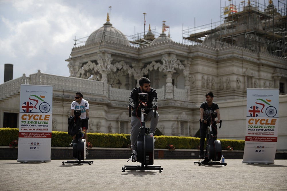 """People take part in """"Cycle to Save Lives"""" a 48 hour, non-stop static relay cycle challenge at the BAPS Shri Swaminarayan Mandir, also know as the Neasden Temple, the largest Hindu temple in the UK, in north London, to raise money to help coronavirus relief efforts in India, Saturday, May 1, 2021. The challenge sees people combining at three different venues in the UK, cycling in a static relay the equivalent distance of 7,600 Km, which is the distance from London to Delhi. (AP Photo/Matt Dunham)"""