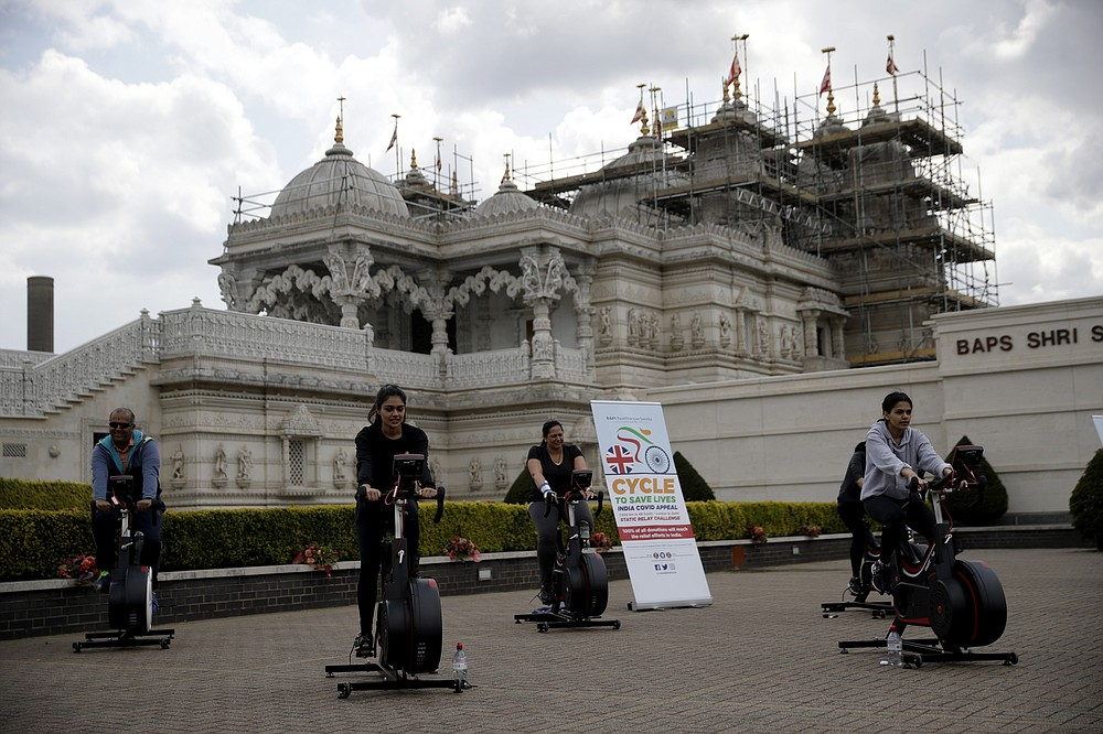 """People take part in """"Cycle to Save Lives"""" a 48 hour, non-stop static relay cycle challenge at the BAPS Shri Swaminarayan Mandir, also know as the Neasden Temple, the largest Hindu temple in the UK, in north London, to raise money to help coronavirus relief efforts in India, Saturday, May 1, 2021. The challenge sees people participating at three different venues in the UK, cycling in a static relay the equivalent distance of 7,600 Km, which is the distance from London to Delhi. (AP Photo/Matt Dunham)"""