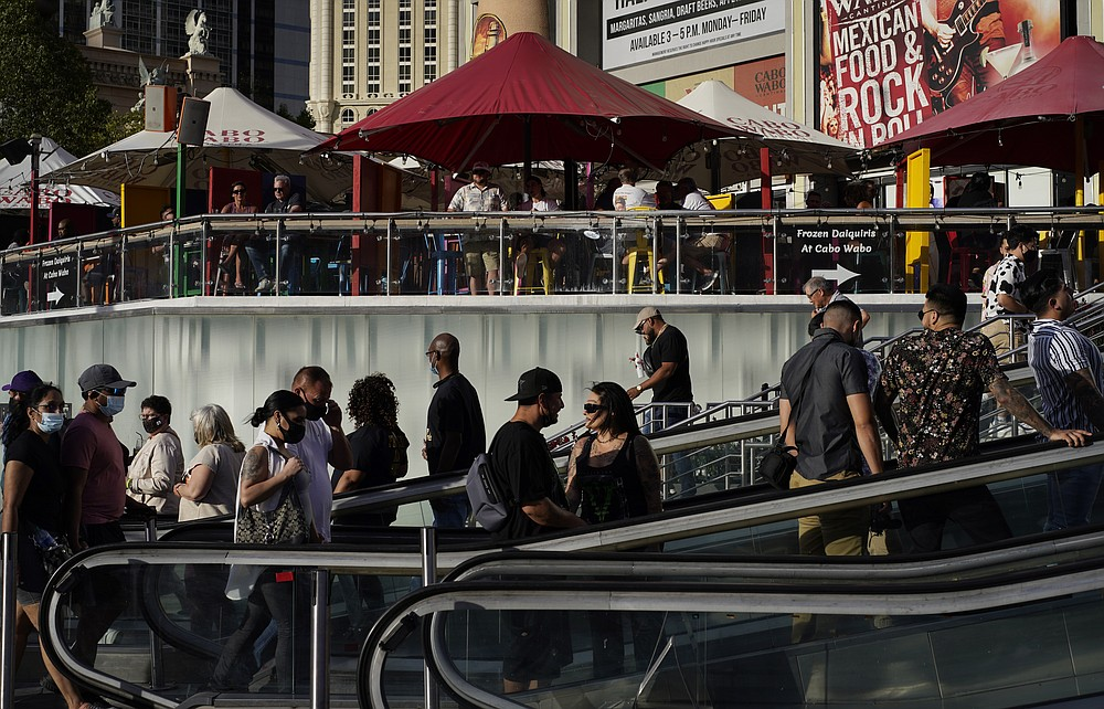 People walk as others dine on the Las Vegas Strip, Saturday, April 24, 2021, in Las Vegas. Las Vegas is bouncing back to pre-coronavirus pandemic levels, with increases in airport passengers and tourism. (AP Photo/John Locher)