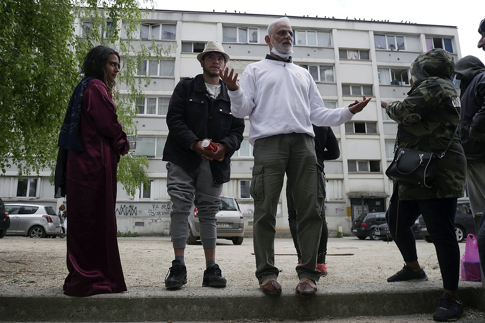"Founder of 'Laissez Les Servir' (Let Them Serve) Nourouddine Abdoulhoussen stands in front of a building in the Fauvettes projects during food distribution, Pierrefitte-sur-Seine, north of Paris, Thursday, April 29, 2021. Nourouddine Abdoulhoussen, a former member of the 8th Marine Infantry Parachute Regiment, runs a tight ship, reaching into his years in the military to inculcate in his proteges, youths from poor French suburbs, confidence, courage and love of France. To the youth in (Let Them Serve) the white-bearded 53-year-old leader with the booming voice is ""the Captain."" (AP Photo/Thibault Camus)"