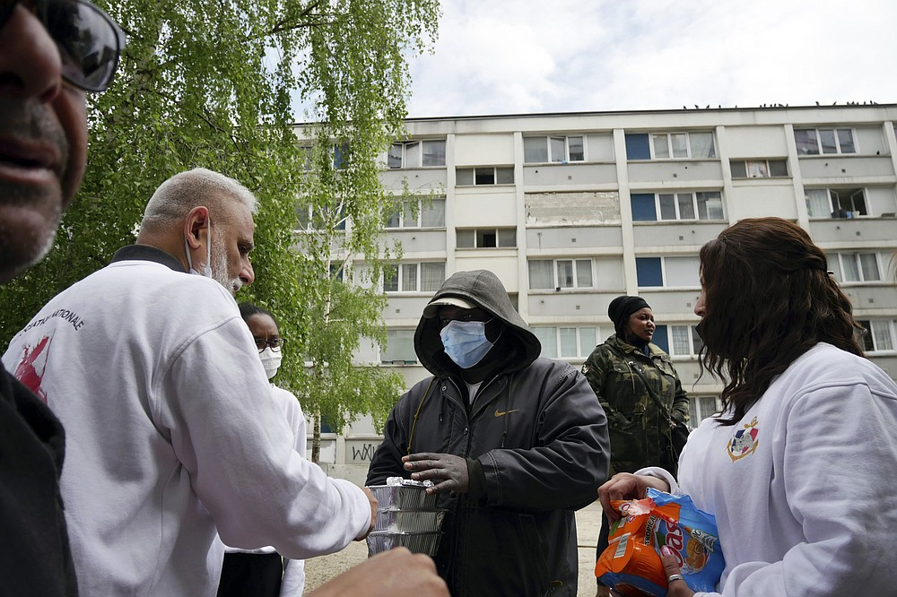 "Founder of 'Laissez Les Servir' (Let Them Serve) Nourouddine Abdoulhoussen, left, and member Mina distribute food in the Fauvettes projects, Pierrefitte-sur-Seine, north of Paris, Thursday, April 29, 2021. Nourouddine Abdoulhoussen, a former member of the 8th Marine Infantry Parachute Regiment, runs a tight ship, reaching into his years in the military to inculcate in his proteges, youths from poor French suburbs, confidence, courage and love of France. To the youth in (Let Them Serve) the white-bearded 53-year-old leader with the booming voice is ""the Captain."" (AP Photo/Thibault Camus)"