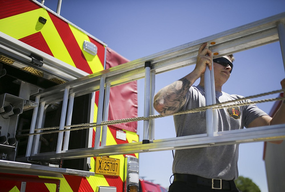 Firefighter Hayden Johnson inspects a ladder, Friday, April 30, 2021 at the Lowell Fire Department in Lowell. Lowell will hold a special election May 10 for voters to extend a current 1 cent sales tax which funds about 70 percent of the city's operating budget. A bulk of the money goes to the fire department, police department and roads. Check out nwaonline.com/210501Daily/ for today's photo gallery.  (NWA Democrat-Gazette/Charlie Kaijo)
