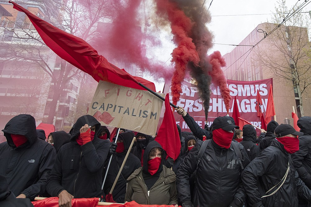"Hooded participants of the ""Revolutionary May Day Demonstration"" march in streets in Frankfurt Saturday, May 1, 2021. (Boris Roessler/dpa via AP)"