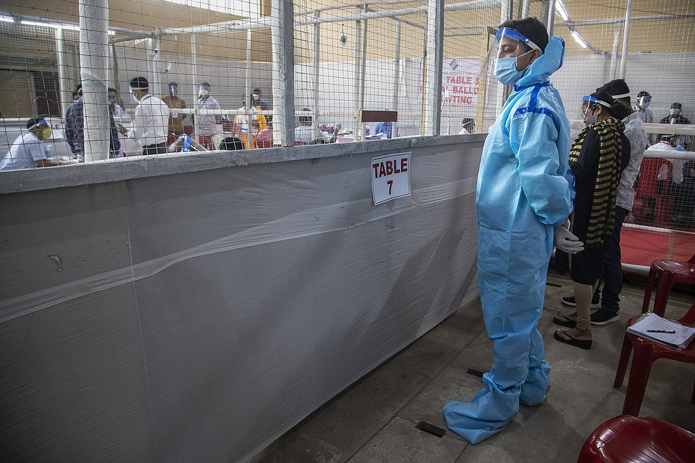 A counting agent stands in protective suit during the counting of votes of Assam state assembly election in Gauhati, India, Sunday, May 2, 2021. With Indian hospitals struggling to secure a steady supply of oxygen, and more covid-19 patients dying amid the shortages, a court in New Delhi said it would start punishing government officials for failing to deliver the life-saving items. (AP Photo/Anupam Nath)
