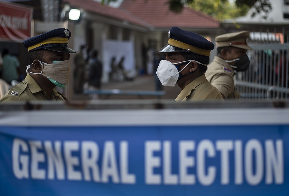 Indian policemen guard at a vote counting center for the state legislature elections amid a weekend lockdown to curb the spread of coronavirus Kochi, Kerala state, India, Sunday, May 2, 2021. (AP Photo/R S Iyer)
