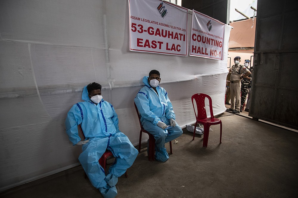 Counting agents in protective suits take rest during the counting of votes of Assam state assembly election in Gauhati, India, Sunday, May 2, 2021. With Indian hospitals struggling to secure a steady supply of oxygen, and more covid-19 patients dying amid the shortages, a court in New Delhi said it would start punishing government officials for failing to deliver the life-saving items. (AP Photo/Anupam Nath)