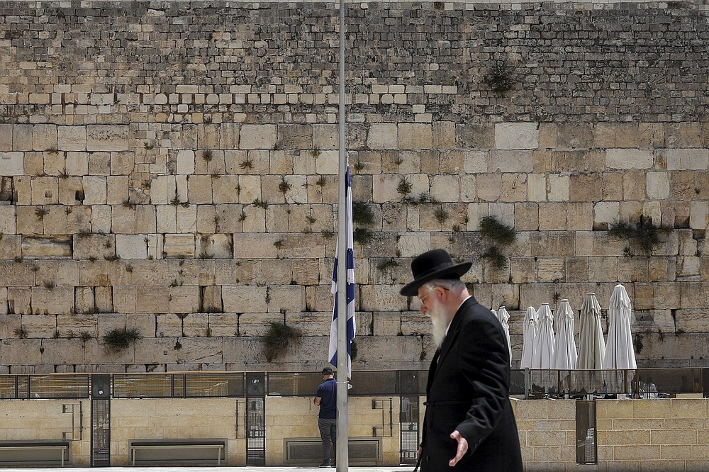 Israel's national flag is lowered to half-mast as the country observes a day of mourning after the death of 45 ultra-Orthodox Jews in a stampede at a religious festival at Mt. Meron last Friday, at the plaza in front of the Western Wall, Judaism's holiest prayer site, in Jerusalem's Old City, Sunday, May 2, 2021. Officials came under growing scrutiny Sunday for ignoring warnings about safety lapses at one of Israel's most visited holy sites, as the country mourned 45 ultra-Orthodox Jews killed in a stampede at a festival there. (AP Photo/Mahmoud Illean)