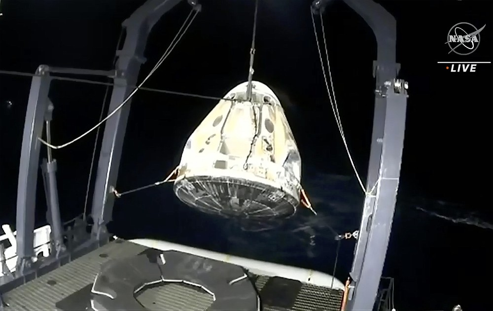 In this image made from NASA TV video, the SpaceX Dragon capsule is retrieved from the Gulf of Mexico near the Florida Panhandle early Sunday, May 2, 2021. SpaceX returned four astronauts from the International Space Station on Sunday, making the first U.S. crew splashdown in darkness since the Apollo 8 moonshot. (NASA TV via AP)
