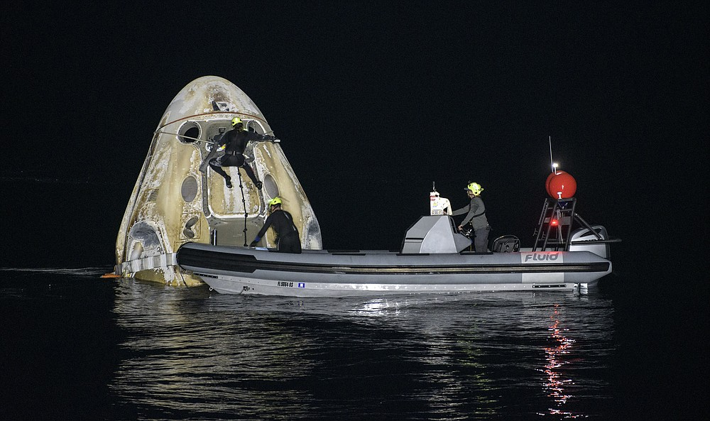 Support teams work around the SpaceX Crew Dragon Resilience spacecraft shortly after it landed with NASA astronauts Mike Hopkins, Shannon Walker, and Victor Glover, and Japan Aerospace Exploration Agency (JAXA) astronaut Soichi Noguchi aboard in the Gulf of Mexico off the coast of Panama City, Florida, Sunday, May 2, 2021. NASA's SpaceX Crew-1 mission was the first crew rotation flight of the SpaceX Crew Dragon spacecraft and Falcon 9 rocket with astronauts to the International Space Station as part of the agency's Commercial Crew Program. (Bill Ingalls/NASA via AP)