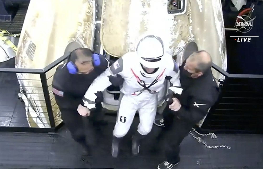 In this image made from NASA TV video, Commander Mike Hopkins egresses the SpaceX Dragon capsule after being retrieved from the Gulf of Mexico near the Florida Panhandle early Sunday, May 2, 2021. SpaceX returned four astronauts from the International Space Station on Sunday, making the first U.S. crew splashdown in darkness since the Apollo 8 moonshot. (NASA TV via AP)