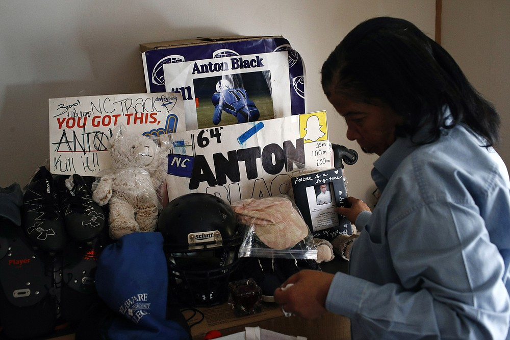 FILE - In this Jan. 28, 2019 file photo, Jennell Black, mother of Anton Black, looks at a collection of her son's belongings at her home in Greensboro, Md. Anton Black, 19, died after a struggle with three officers and a civilian outside the home in September 2018.  Cases involving police use of force often include questions about the internal records of the officers involved, records that in most cases are off-limits to the press and public.  Lawmakers in at least 13 states have considered bills this year to make those records more publicly available. (AP Photo/Patrick Semansky, File)