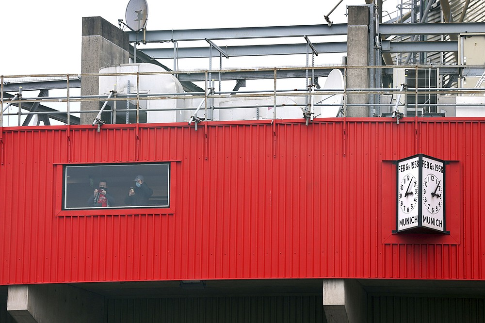 Fans inside the stadium look out from a window as they protest against the Glazer family, owners of Manchester United, before their Premier League match against Liverpool at Old Trafford, Manchester, England, Sunday, May 2, 2021. Manchester United supporters have stormed into the stadium and onto the pitch ahead of Sunday's game against Liverpool as fans gathered outside Old Trafford to protest against the ownership.  (Barrington Coombs/PA via AP)