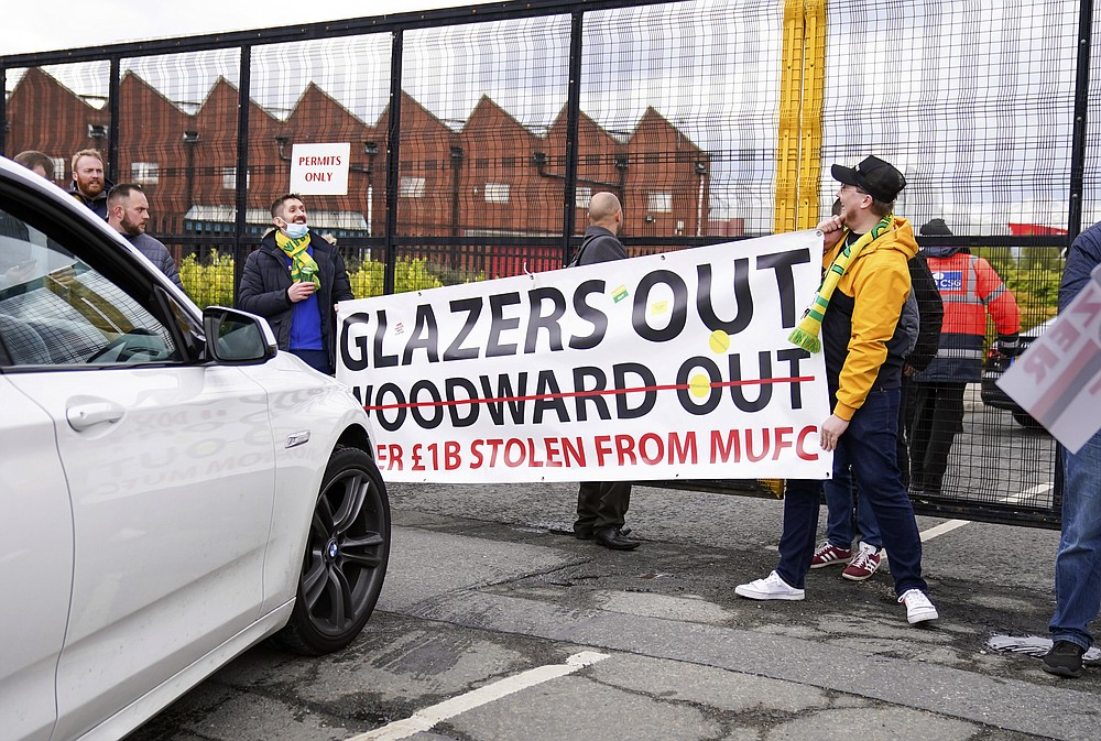 Manchester United fans prevent cars arriving at Old Trafford, during a protest against the Glazer family, owners of Manchester United, before their Premier League match against Liverpool at Old Trafford, Manchester, England, Sunday, May 2, 2021. Manchester United supporters have stormed into the stadium and onto the pitch ahead of Sunday's game against Liverpool as fans gathered outside Old Trafford to protest against the ownership. (AP Photo/Dave Thompson)