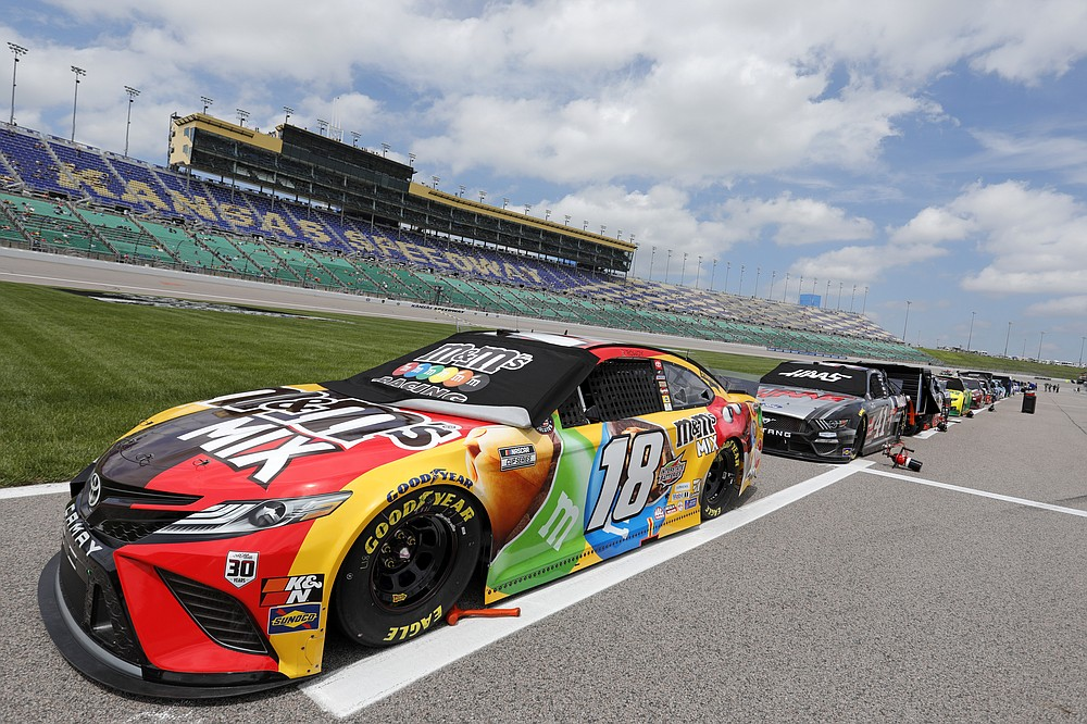 Kyle Busch's 18 car and others are parked along pit road before the start of a NASCAR Cup Series auto race at Kansas Speedway in Kansas City, Kan., Sunday, May 2, 2021. (AP Photo/Colin E. Braley)
