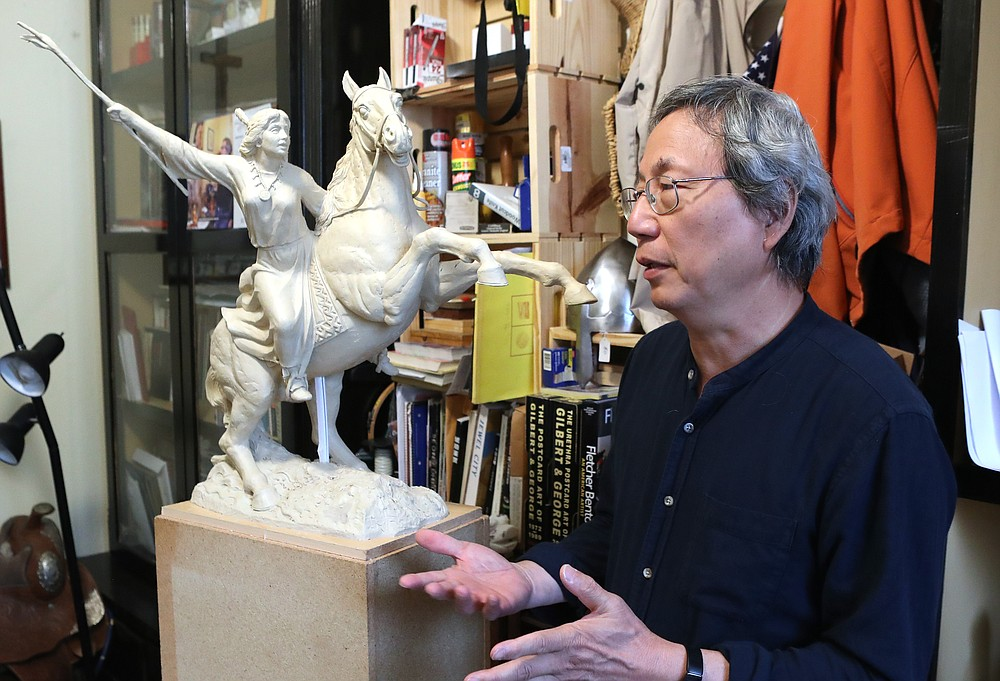Artist Longhua Xu discusses his latest sculpture in his Hot Springs studio Wednesday. - Photo by Richard Rasmussen of The Sentinel-Record