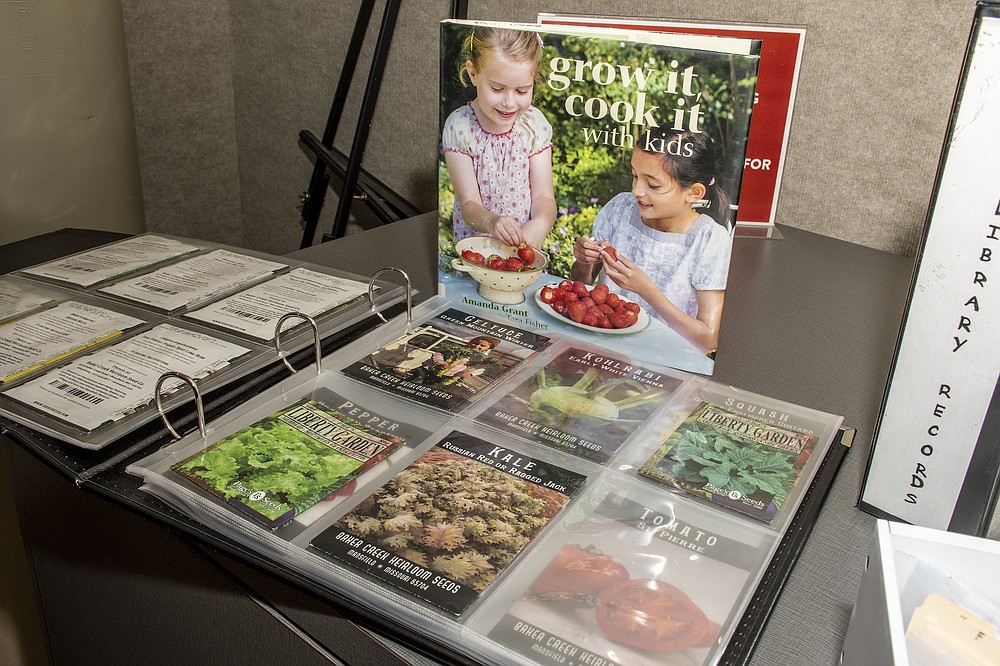 Seed packets are kept in a binder that contains information about the plants that will grow from the seeds. (Arkansas Democrat-Gazette/Cary Jenkins)