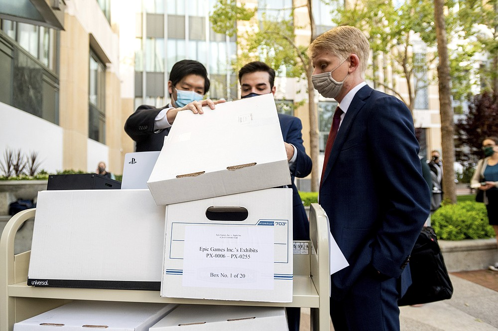 Members of Epic Games' legal team roll exhibit boxes into the Ronald V. Dellums building in Oakland, Calif., for the company's lawsuit against Apple on Monday, May 3, 2021. Epic, maker of the video game Fortnite, charges that Apple has transformed its App Store into an illegal monopoly. (AP Photo/Noah Berger)