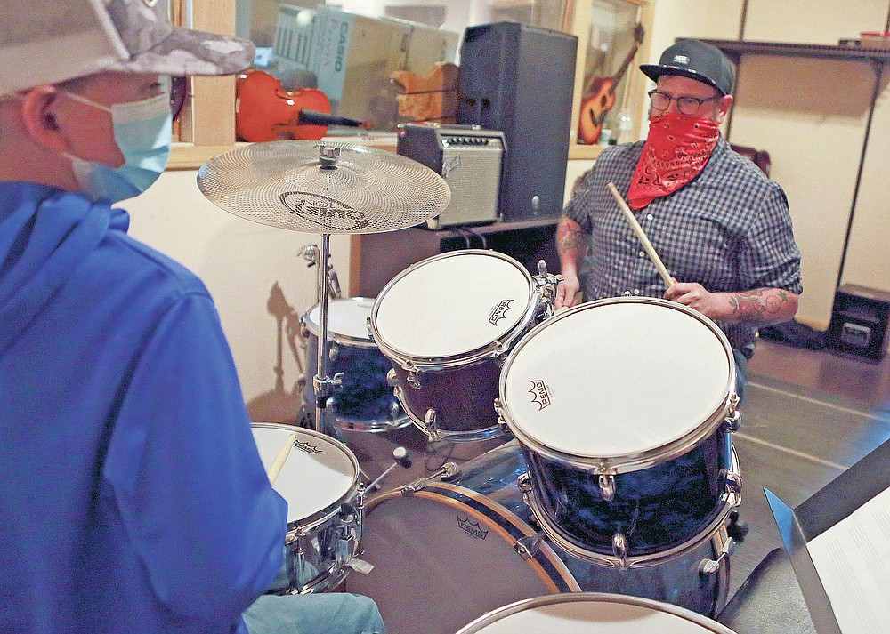 Intermediate drummer student Sean Vogt, left, practices with his music instructor Jim Bohon of Bridge Kaldro Music in Christiansburg, Va., Thursday, April 22, 2021. It was Bridge Kaldro Music that that touched off a battle royale with signs, challenging businesses to poke silly fun at one another. It has quickly spread across town and gone viral online. (Matt Gentry/The Roanoke Times via AP)