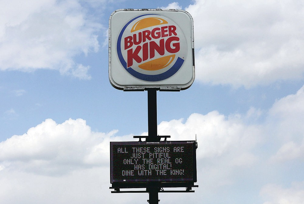 Burger King takes a sign war shot with their digital display sign in Christiansburg, Va., Thursday, April 22, 2021. It was Bridge Kaldro Music that that touched off this sign battle royale, challenging businesses to poke silly fun at one another. It has quickly spread across town and gone viral online. (Matt Gentry/The Roanoke Times via AP)