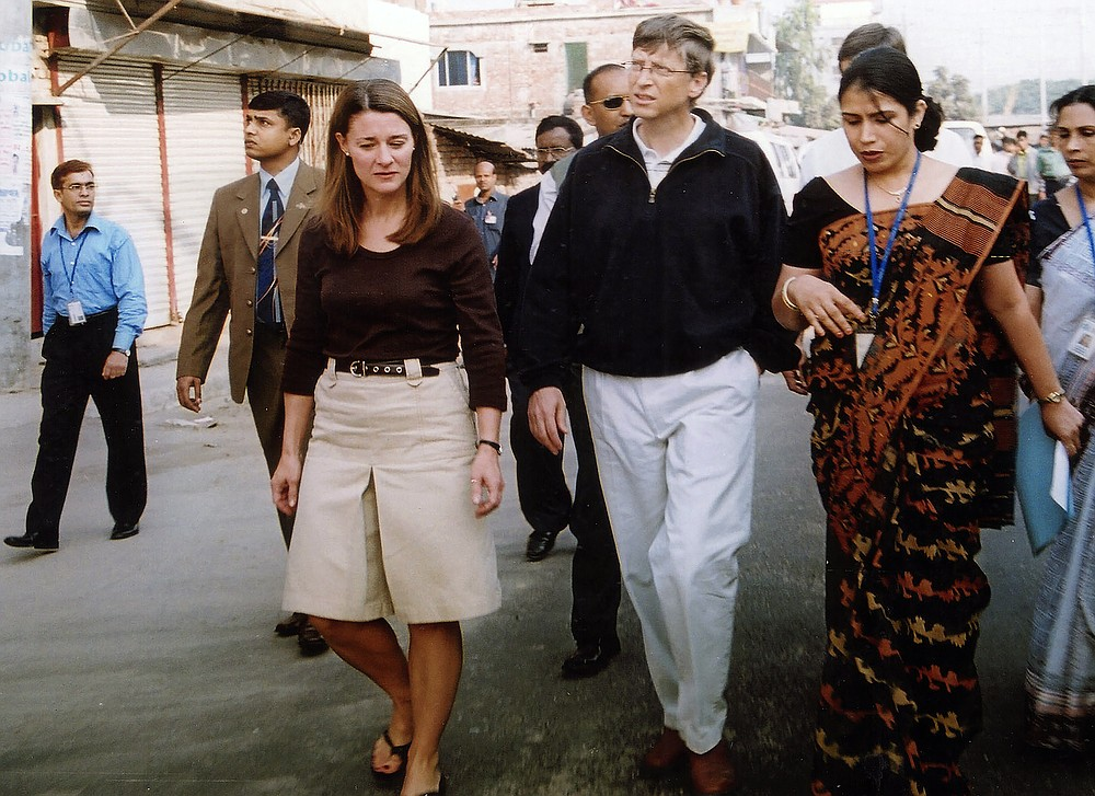 FILE - In this Dec. 5, 2005, file photo, Bill Gates, founder and chairman of Microsoft Corp., center, and his wife Melinda, left, walk on a street in Dhaka, Bangladesh. The couple announced Monday, May 3, 2021, that they are divorcing. The Microsoft co-founder and his wife, with whom he launched the world's largest charitable foundation, said they would continue to work together at The Bill & Melinda Gates Foundation. (AP Photo/Gazi Sarwar, File)