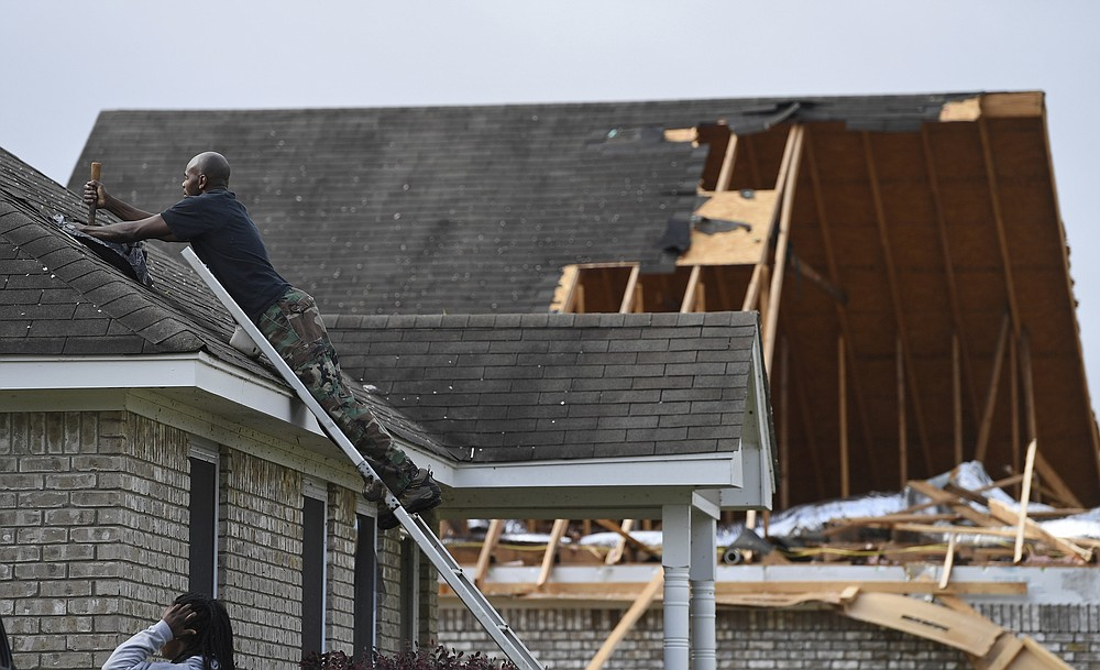 Alfred Lee covers a damaged spot on the roof of his home on Elvis Presley Drive in Tupelo, Miss., Monday, May 3, 2021. Multiple tornadoes were reported across Mississippi on Sunday, causing some damage but no immediate word of injuries.(AP Photo/Thomas Graning)