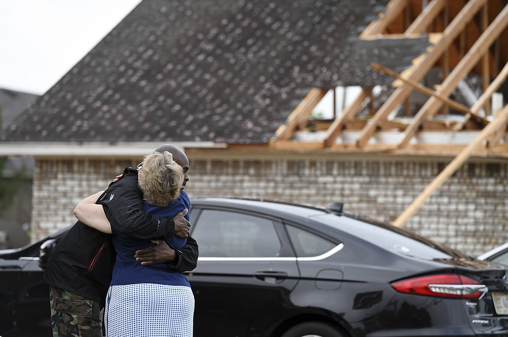 Neighbors Alfred Lee and Grace Bazzy hug in front of another neighbor's damaged home along Elvis Presley Drive in Tupelo, Miss., Monday, May 3, 2021. Multiple tornadoes were reported across Mississippi on Sunday, causing some damage but no immediate word of injuries. (AP Photo/Thomas Graning)