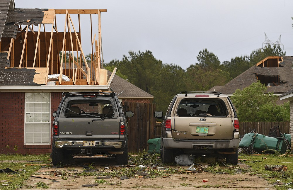 """Damaged homes and vehicles are seen along Elvis Presley Drive in Tupelo, Miss., Monday, May 3, 2021. A line of severe storms rolled through the state Sunday afternoon and into the nighttime hours. Late Sunday, a """"tornado emergency"""" was declared for Tupelo and surrounding areas. (AP Photo/Thomas Graning)"""