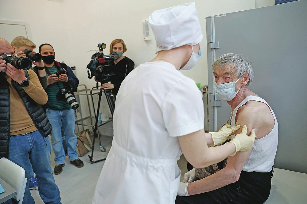 An elderly man wearing a face mask to protect against coronavirus receives a shot of Russia's Sputnik V coronavirus vaccine in front of working visual journalists at a vaccination point in Moscow, Russia, Wednesday, April 7, 2021. To boost the demand, officials in Moscow this week started offering 1,000-ruble ($13) coupons to people over 60 for getting vaccinated. So far, the incentive hasn't elicited a lot of enthusiasm among elderly Muscovites. (AP Photo/Pavel Golovkin)