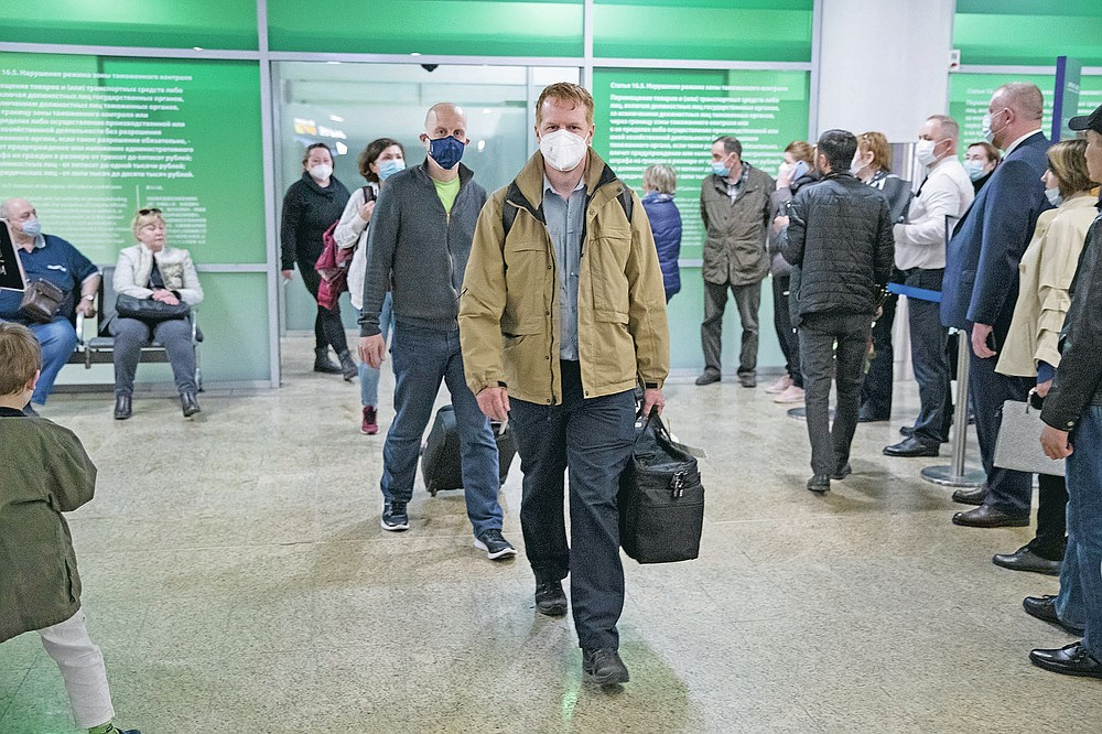 Germany's Enno Lenze, center, and Uwe Keim, center left, both wearing face masks to protect agains coronavirus, enter the hall after arriving at Sheremetyevo airport, outside Moscow, Russia, Thursday, April 15, 2021. The abundance of vaccines in the Russian capital has been drawing in vaccine tourists, not just from other regions, where the wait for a shot is longer, but foreigners, too. A group of Germans traveled to Moscow earlier this month and got their first shots right at their hotel. (AP Photo/Pavel Golovkin)