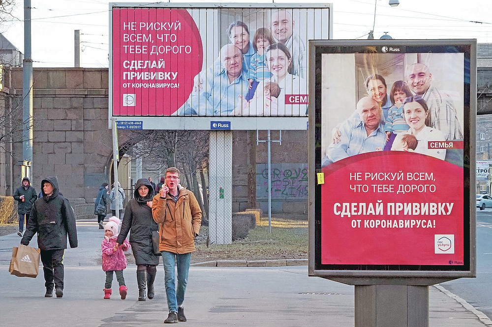 """People walk past posters reading """"Do not risk everything that is dear to you. Get vaccinated against coronavirus"""" in St. Petersburg, Russia, Saturday, April 3, 2021. Russia has boasted about being the first country in the world to authorize a coronavirus vaccine and rushed to roll it out earlier than other countries, even as large-scale testing necessary to ensure its safety and effectiveness was still ongoing. (AP Photo/Dmitri Lovetsky)"""