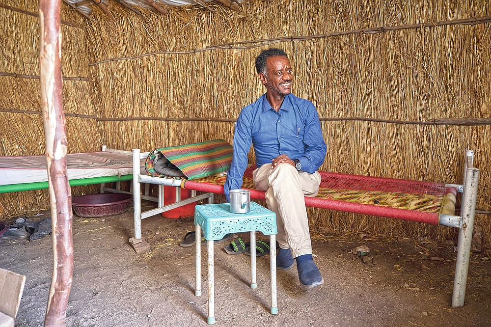 Surgeon and doctor-turned-refugee, Dr. Tewodros Tefera, takes a cigarette break inside his shelter at the Sudanese Red Crescent clinic where he works, in Hamdayet, eastern Sudan, near the border with Ethiopia, on March 22, 2021. (AP Photo/Nariman El-Mofty)