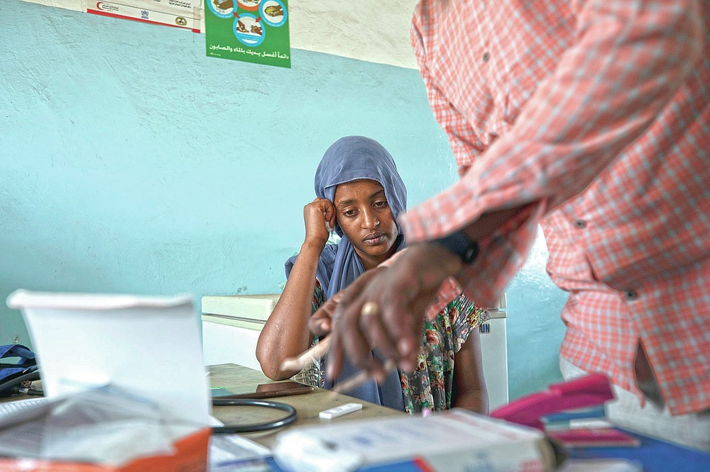 Surgeon and doctor-turned-refugee, Dr. Tewodros Tefera, prepares a malaria test for 23-year-old Tigrayan refugee Hareg from Mekelle, Ethiopia, at the Sudanese Red Crescent clinic in Hamdayet, eastern Sudan, near the border with Ethiopia, on March 17, 2021. (AP Photo/Nariman El-Mofty)