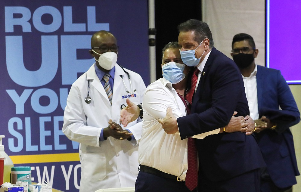 Gov. Andrew Cuomo embraces Radhames Rodriguez, President of United Bodegas of America, after Rodriguez received a Pfizer COVID-19 vaccination shot at an event to announce five new walk-in pop-up COVID-19 vaccination sites for New York Bodega, grocery store and supermarket workers in the Harlem section of New York on Friday, April 23, 2021.  (Mike Segar/Pool Photo via AP)
