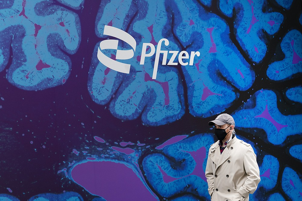 A man walks by Pfizer headquarters, Friday, Feb. 5, 2021 in New York.  Pfizer, buoyed by a huge jump in sales for its COVID-19 vaccine and solid first-quarter performance across most of the company, hiked its 2021 financial forecast after sharply after blowing past Wall Street expectations, Tuesday, May 4. (AP Photo/Mark Lennihan)