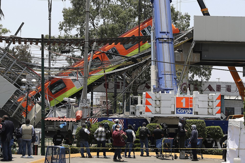 Subways cars are lowered to ground from a collapsed elevated section of the metro, in Mexico City, Tuesday, May 4, 2021. An elevated section of the Mexico City metro collapsed late Monday, killing at least 23 people and injuring at least 79, city officials said. (AP Photo/Marco Ugarte)