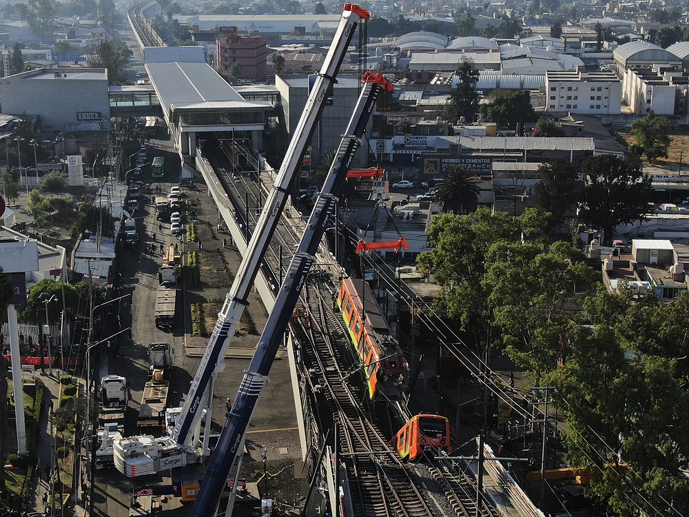 Subway cars dangle at an angle from a collapsed elevated section of the metro, in Mexico City, Tuesday, May 4, 2021. The elevated section of the metro's Line 12 collapsed late Monday killing at least 23 people and injuring at least 79, city officials said. (AP Photo/Fernando Llano)