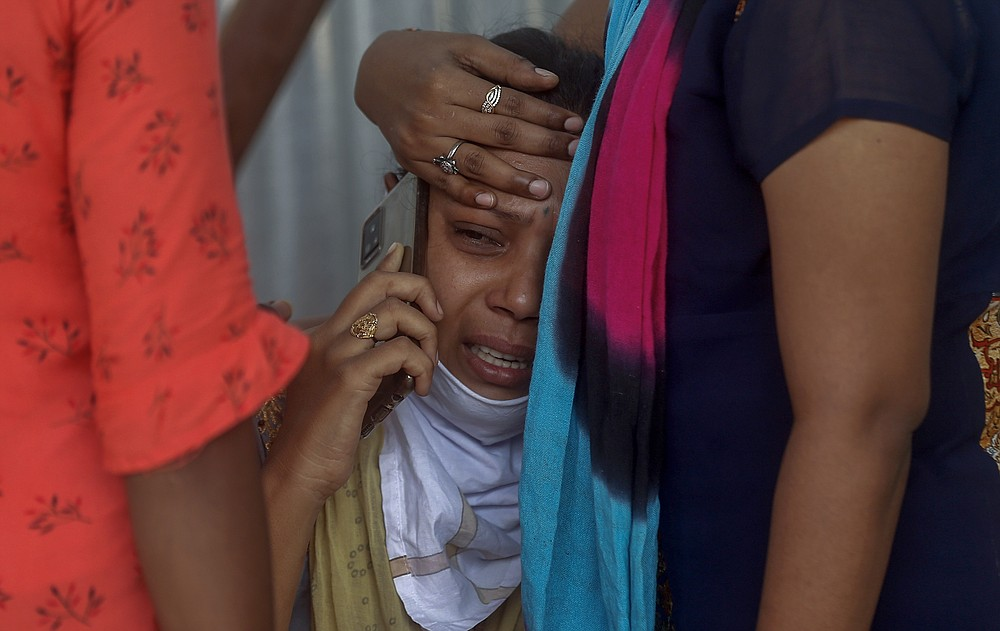 FILE - In this May. 3, 2021, file photo, relatives of a person who died of COVID-19 mourn outside a field hospital in Mumbai, India. COVID-19 infections and deaths are mounting with alarming speed in India with no end in sight to the crisis. People are dying because of shortages of bottled oxygen and hospital beds or because they couldn't get a COVID-19 test. (AP Photo/Rafiq Maqbool, File)