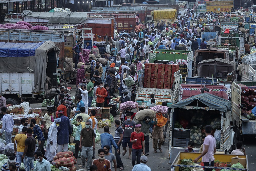Indians crowd a vegetable market in Jammu, India, Tuesday, May 4, 2021. COVID-19 infections and deaths are mounting with alarming speed in India with no end in sight to the crisis. (AP Photo/Channi Anand)