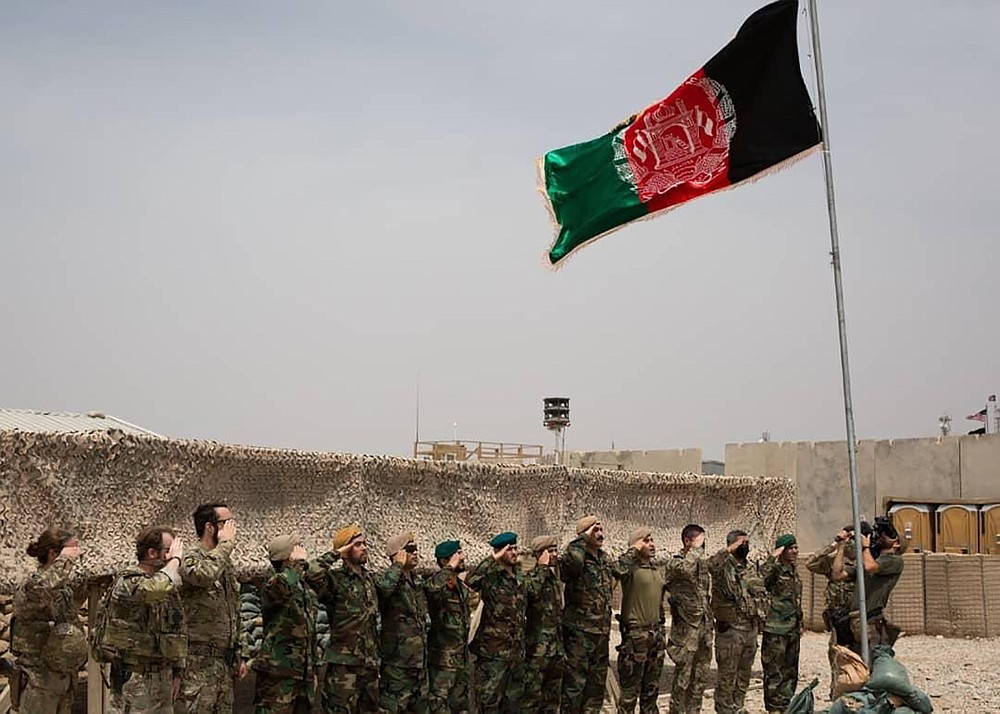 An Afghan flag flies as American and Afghan soldiers salute during a handover ceremony from the U.S. Army to the Afghan National Army, at Camp Anthonic, in Helmand province, southern Afghanistan, Sunday, May 2, 2021. (Afghan Ministry of Defense Press Office via AP)