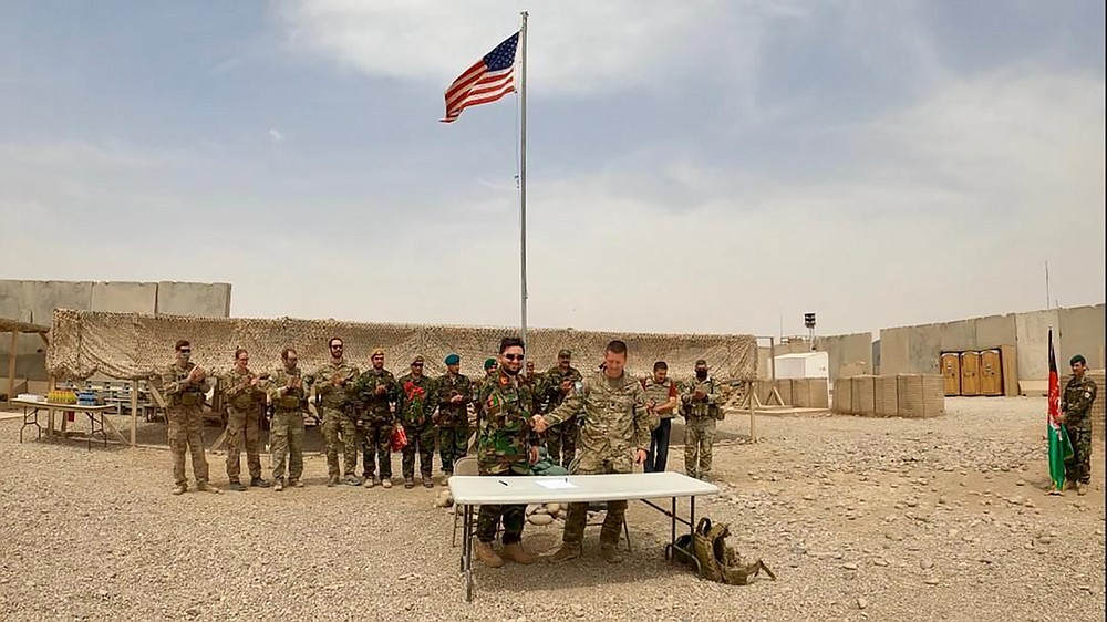 A U.S. flag flies as American and Afghan soldiers attend a handover ceremony from the U.S. Army to the Afghan National Army, at Camp Anthonic, in Helmand province, southern Afghanistan, Sunday, May 2, 2021. (Afghan Ministry of Defense Press Office via AP)