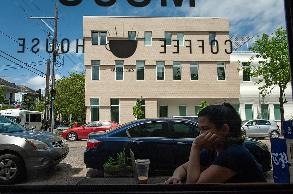 A customer sits at an outdoor table at a coffee shop across the street from the Travelers New Orleans. (Rory Doyle/The New York Times)